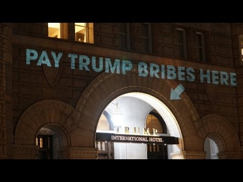 pay bribes here sign projected onto trump
