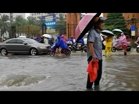 Arab Today, arab today good samaritan guards manhole during a storm in hainan province