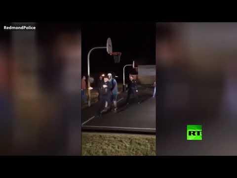 رجال شرطة يشاركون شبانَا في لعب كرة السلة