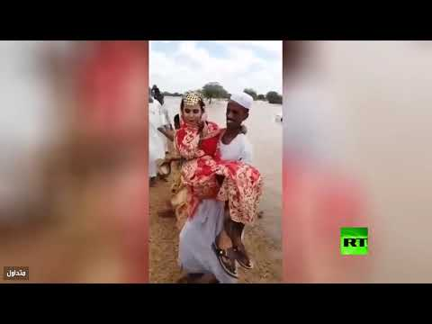 شاهد عريس يحمل عروسته فوق السيول في أحد المدن السودانية